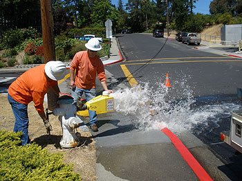 Crew Leader Doug Funk and Utility Worker Jason Schneider open a hydrant.