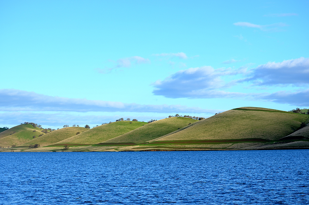 Green hills with the reservoir in front of them