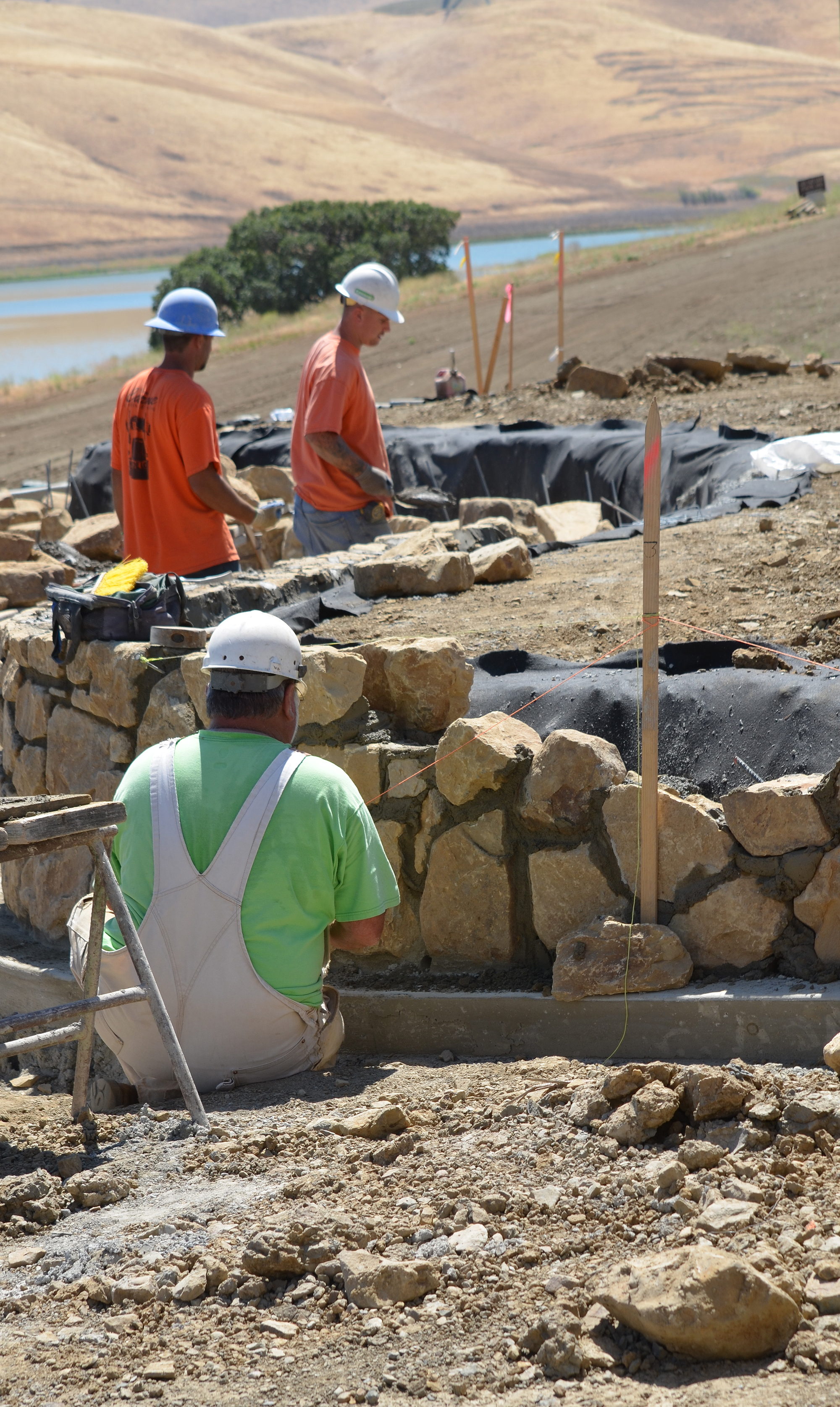 Masonry workers build a new stone wall near the ne