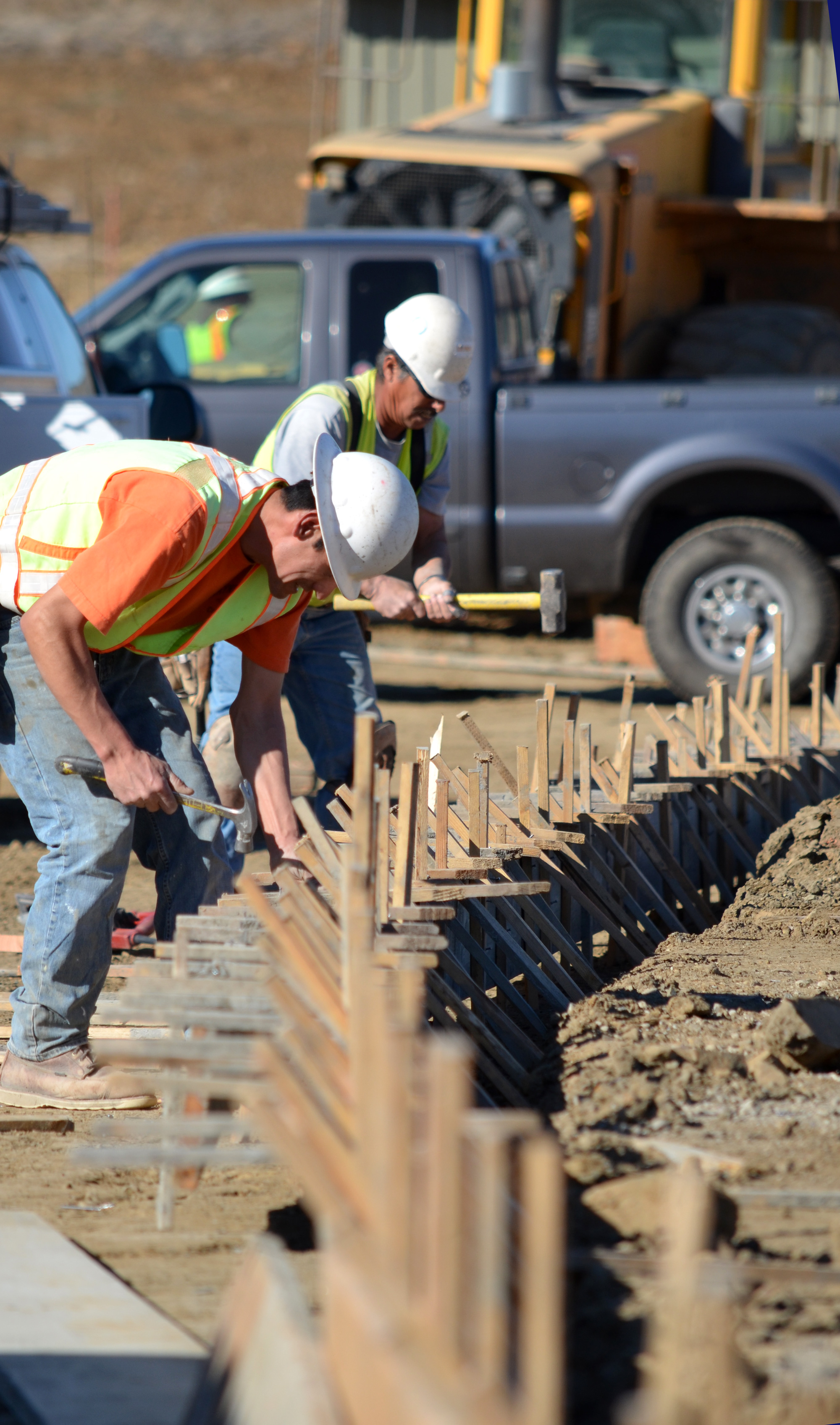 Masonry workers build the forms for a curb outside