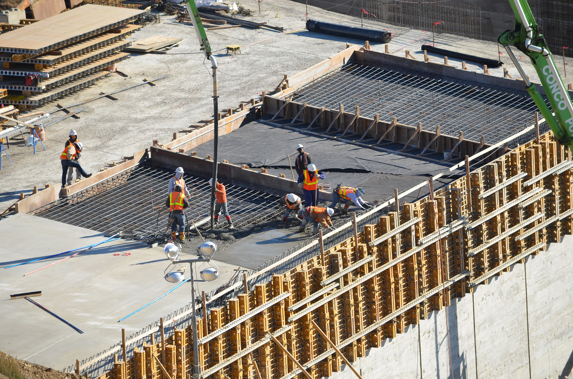 Masonry workers pour and shape concrete