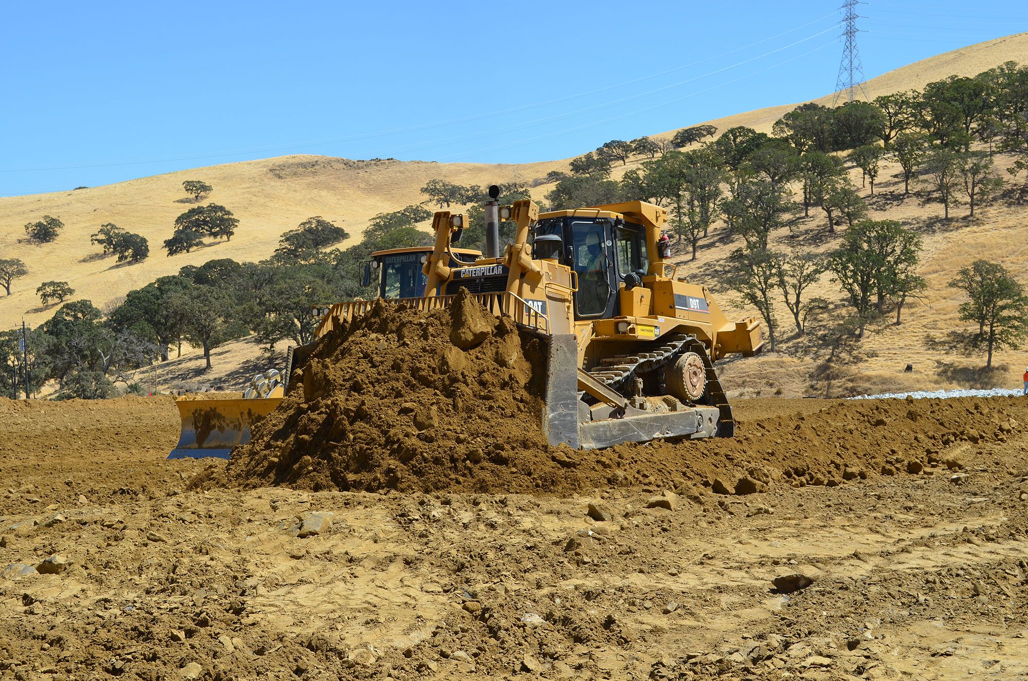 Two massive bulldozers spread new material
