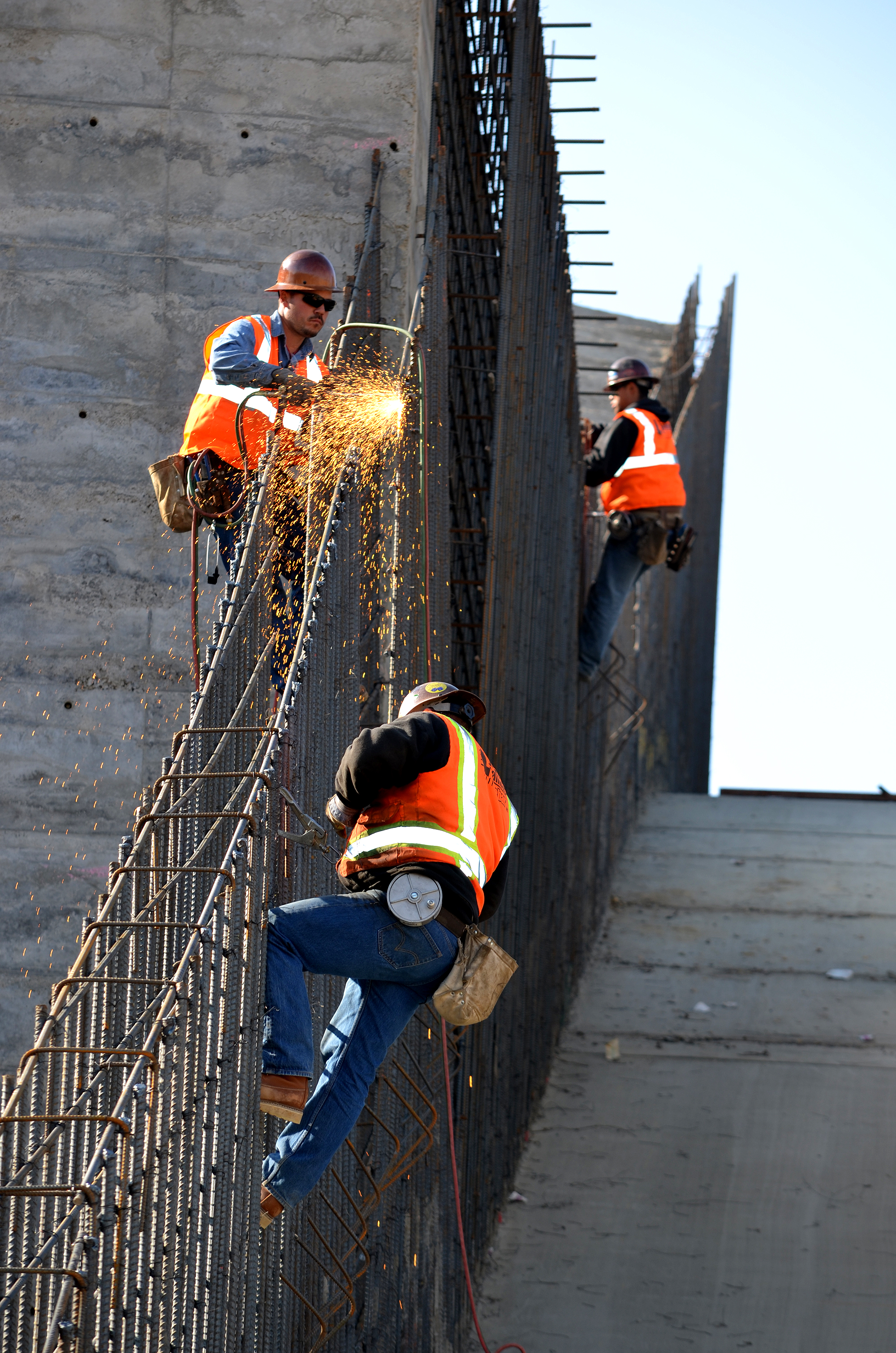 Welders trim rebar on the spillway area