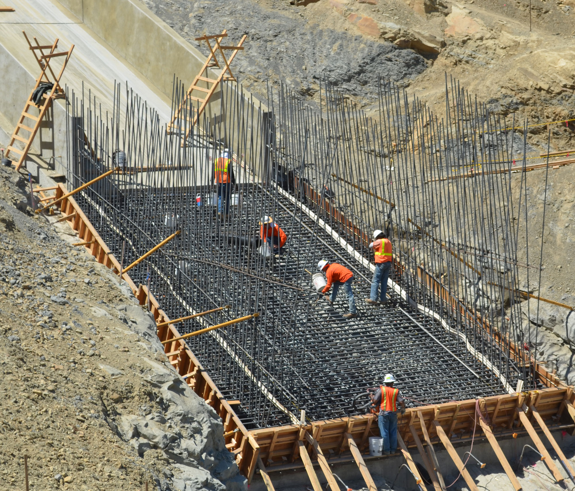 Workers place rebar for the spillway